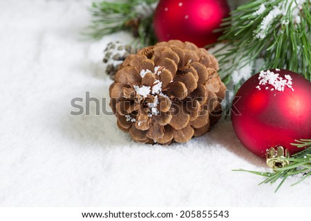 Closeup horizontal view of large pine cone, resting in white snow, with Christmas ornaments and evergreen tree branch in background