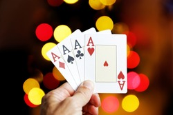 Closeup human hand holding four playing cards aces against colorful lights on blurred background
