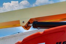 Closeup hydraulic of boom lift. Orange articulated boom lift. Maintenance and repair hydraulic boom lift service. Aerial platform. Telescopic boom lift. Mobile construction crane. Hydraulic cylinder.