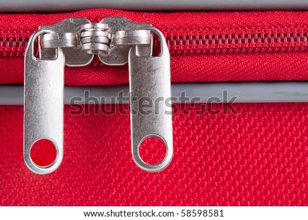 Closeup image from a closed zipper of a red suitcase