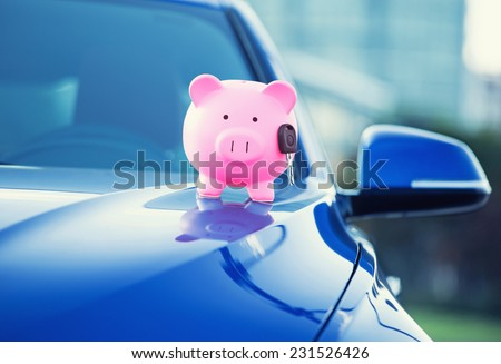 Closeup image new car with piggy bank, key on hood isolated outside corporate building. Dealership offering credit line finance services. Lease automobile purchase financing concept. Financial success
