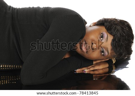 Closeup image of a beautiful African American teen side-laying on her reflection.