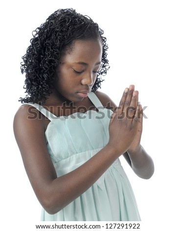 Closeup image of a beautiful young tween with her head bowed, eyes closed and hands clasped in prayer.  On a white background.