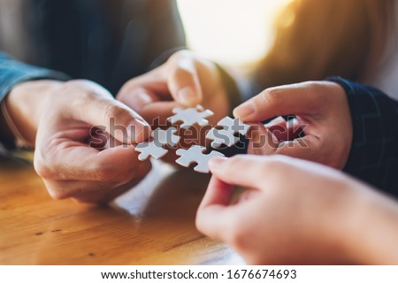 Closeup image of a group of people holding and putting a piece of white jigsaw puzzle together Foto stock ©