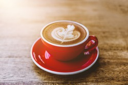 Closeup image of a red cup of hot latte coffee with latte art on wooden table
