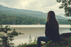 Closeup image of an asian woman sitting alone by the river with sky and mountain background