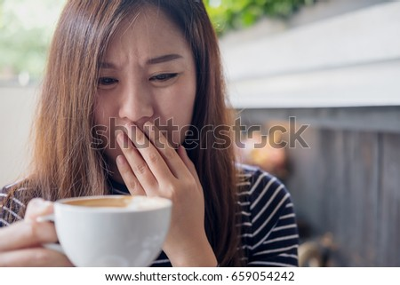 Closeup image of Asian woman holding hot coffee with feeling strange and smelling bad in coffee shop