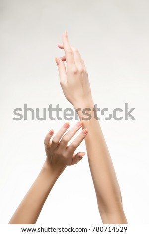 Closeup image of beautiful woman's hands with light pink manicure on the nails. Cream for palms, manicure and beauty treatment. Elegant and graceful arms with slender graceful fingers. Copy space.