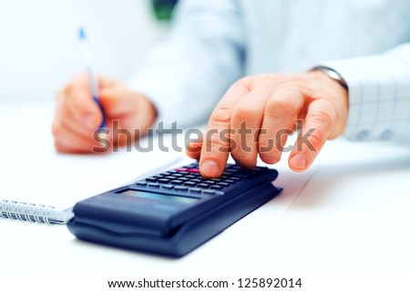 Closeup image of businessman calculating