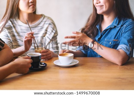 Closeup image of friends enjoyed talking and drinking coffee together in cafe
