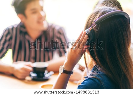 Closeup image of friends enjoyed talking, listening to music with headphone and drinking coffee together in cafe