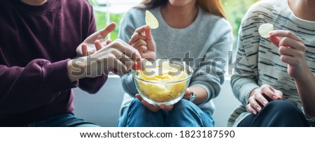 Closeup image of friends sharing and eating potato chips at home party together Foto stock ©
