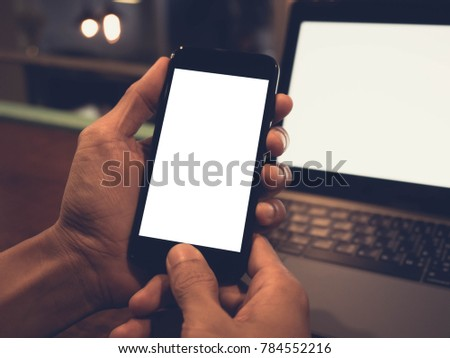 Closeup  image of hand holding black mobile phone with blank white screen and laptop background in blur coffee cafe background #784552216