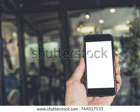 Closeup  image of hand holding black mobile phone with blank white screen in coffee cafe #744017533