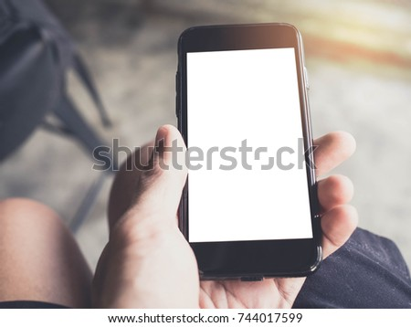 Closeup  image of hand holding black mobile phone with blank white screen in coffee shop #744017599