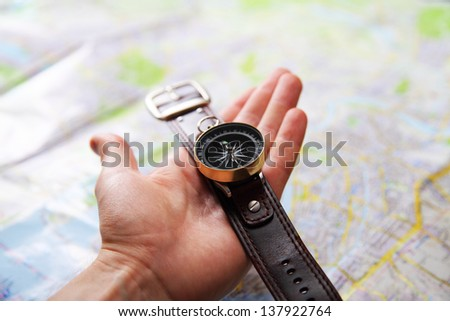 Closeup image of hand with magnetic compass over a map