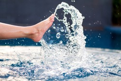 Closeup image of legs and bare feet kicking and splashing water in the pool