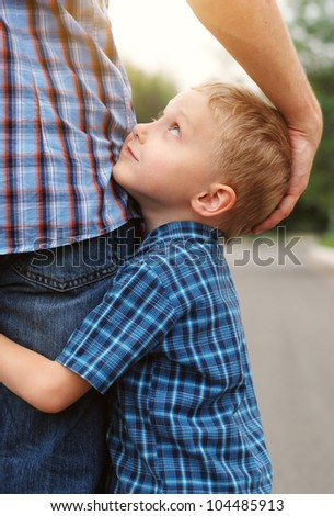 Closeup image of little son tender hugging his father