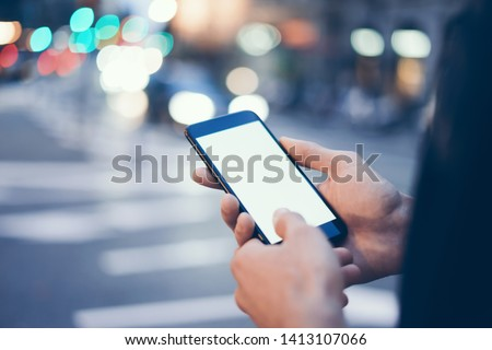 Closeup image of male hand holding modern smartphone with blank screen. Mockup ready for text message or content. Man's hands with cellphone. Empty display. Night street, bokeh light