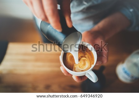 Closeup image of male hands pouring milk and preparing fresh cappuccino, coffee artist and preparation concept, morning coffee