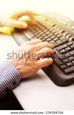 Closeup image of male hands typing