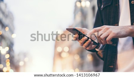 Closeup image of male hands with smartphone at night on city street, searching internet or social networks, hipster man typing an sms message on chat, bokeh lights Foto stock ©