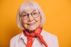 Closeup image of old cheerful woman with white hair and gray eyes wearing round glasses, white blouse, orange scarf or cravat. Woman standing isolated over orange background and smiling
