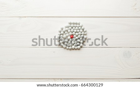 Closeup image of one red sphere among lots of white ones. Concept of difference