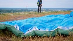 Closeup image of parachute wing lying on grass on field after parachutist landing.