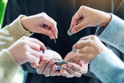 Closeup image of people putting coins into another people's hands