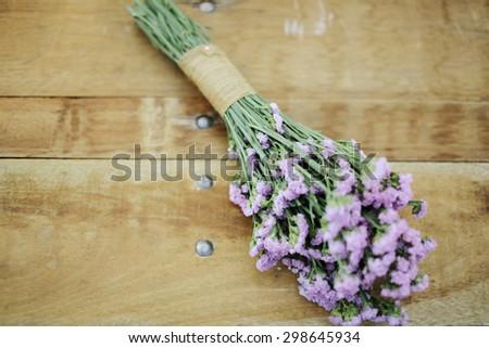 Closeup image of purple wedding flower bouquet decoration on wooden background, wedding concept