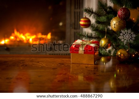 Stock Photo Closeup image of red gift box on wooden table in front of burning fireplace and Christmas tree