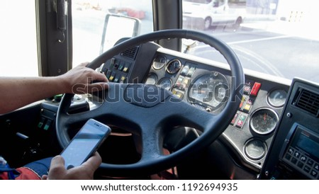 Closeup image of truck driver typing on smartphone while driving. Danger in transport. Irresponsible driver #1192694935