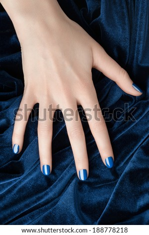Closeup image of woman hand with beautiful blue manicure over blue velvet
