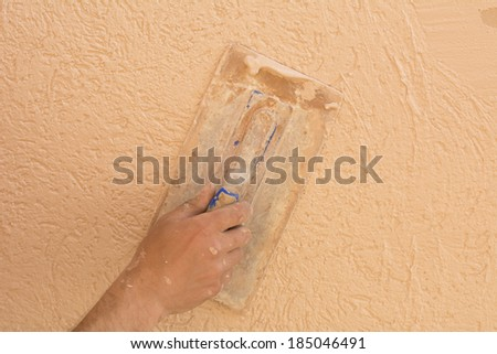 Closeup image of worker hand spreading colored mortar over styrofoam insulation with trowel  #185046491