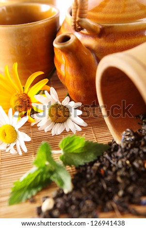 Closeup image with chinese teapot, daisy flowers and mint
