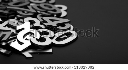 closeup image with pile metal numbers on black background