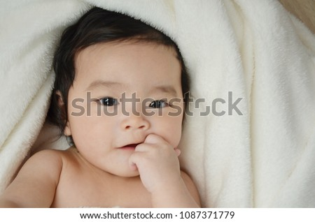 Closeup infant baby girl is sucking fingers