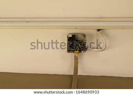 Closeup inside electrical junction box attached to ceiling, showing wires connection, the box joined to flexible conduit which connected to fluorescent lamp