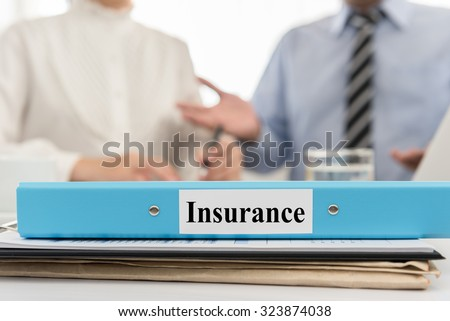 closeup insurance file with two business people meeting in office. Concept of  insurance.