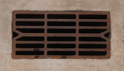 Closeup iron grate of drainage system, image of storm water sewer system on a sunny summer day. Metal drain cover road. Storm water drain. Global warming