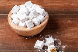 Closeup isolated image of Traditional Turkish delight, a popular dessert in Turkey with gummy like consistency and nut pieces inside. Cubes of the sweet is put in a wooden bowl on table top.