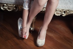 closeup leg caption of model girl wearing white dress sitting on victorian sofa using left shoe holding  hand over right toes