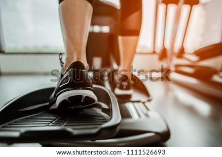 Closeup leg of cardio workout on an elliptical.people working out on an elliptical trainer in gym.Back view