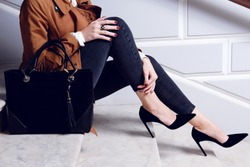 Closeup legs fashionable woman wear black high heels shoes and sitting on the white stairs. Stylish fall and spring outfit