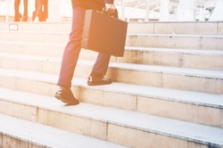 Closeup legs of Businessman Walking Stepping up the Stairs in rush hour to work in a hurry. During the first morning of work.business growth up success start up business concept