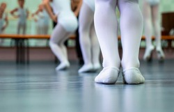 closeup legs of little ballerinas group in white shoes practicing in ballet studio. Young girls training elements of classical dance exercise. Childhood, dancing, lifestyle concept