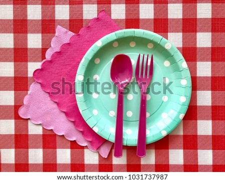 Closeup light green polka dot paper plate with pink plastic spoon,fork and napkin on red & white checkered pattern background.The concept of Birthday party accessories,picnic utensil.Selective focus. #1031737987