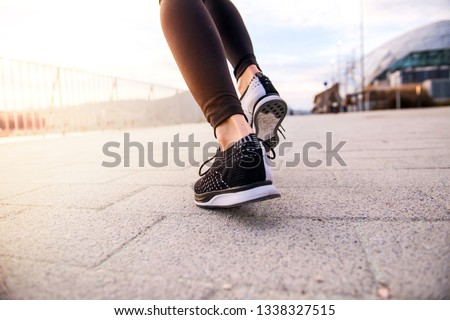 Closeup look of the shoes of a jogging women #1338327515