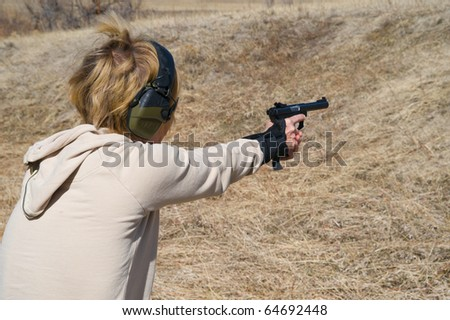 Closeup looking over a woman's shoulder taking target practice with a pistol.
